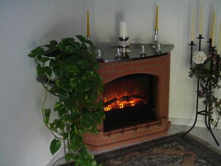 Kunstvolle Handarbeit und ein täuschend echtes Feuer bietet diese Eck-Elektrokamin. Für eine Ecke zum Entspannen.